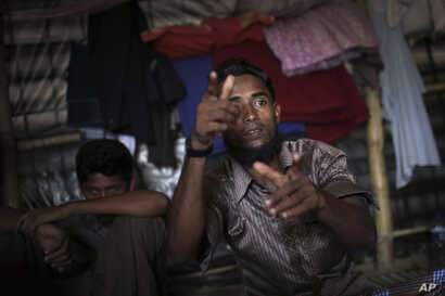 In this Nov. 24, 2017, photo, Li Juhar, who fled to. Bangladesh from Myanmar's Rakhine State, becomes animated, forming both his hands into the shape of guns, when he speaks of soldiers flooding into his village