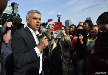 Britain's newly elected mayor Sadiq Khan speaks to supporters as he arrives for his first day at work at City Hall in London, May 9, 2016.