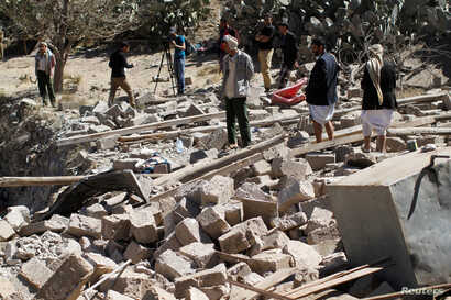 People walk on the rubble of a house destroyed by a Saudi-led airstrike in Sana'a, Yemen, Feb. 2, 2017.