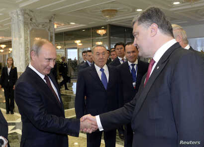 Russian President Vladimir Putin (L) shakes hands with his Ukrainian counterpart Petro Poroshenko at the start of talks in Minsk, Belarus, Aug. 26, 2014.