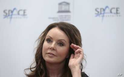 British soprano singer Sarah Brightman listens journalists during news conference in Moscow, Russia, Oct. 10, 2012 to announce that she will become the first-ever global recording artist to take a spaceflight, teaming up with Space Adventures for a j...
