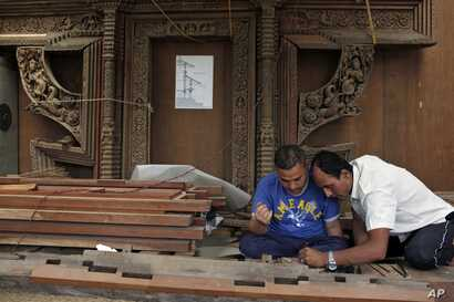 """Silpakars,"" or woodworkers from the Newar ethnic community, work on a restoration project in Lalitpur, Nepal, July 19, 2017. Centuries-old Char Narayan and Hari Shankara temples were destroyed by the massive April 2015 earthquake. A team of dedicate..."