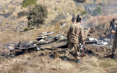 Pakistani soldiers stand next to wreckage of an Indian fighter jet