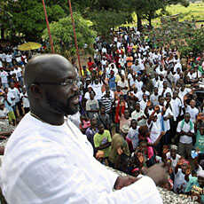 George Weah, a former soccer star and the running mate of presidential candidate Winston Tubman of the Congress for Democratic Change (CDC), stands at the balcony after a news conference at his headquarters in Monrovia, November 5, 2011