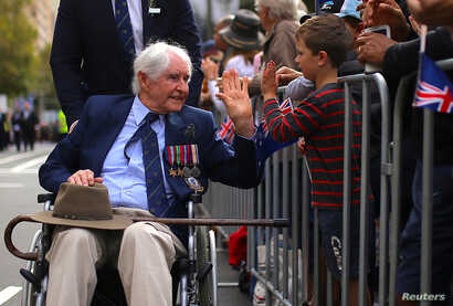 A boy greets a veteran in a wheelchair during the annual ANZAC (Australian and New Zealand Army Corps) Day march through central Sydney, Australia, April 25, 2017.