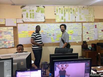 Kiro'o Games Games Designer Dominique Yakan and Chief Executive Officer Olivier Madiba pose in front of the team's ideas wall in Kiro'o headquarters, Yaounde, Cameroon, July 10, 2018.