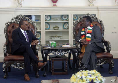 FILE - United States Ambassador to Zimbabwe Brian Nichols, left, is seen during a courtesy call with Zimbabwean President elect Emmerson Mnangagwa at his official residence State House in Harare, Aug, 15, 2018. Nichols emphasized the need to respect ...