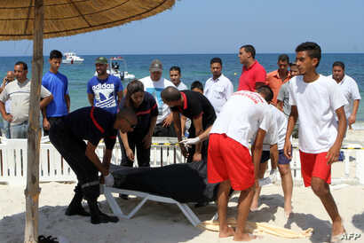 Tunisian lifeguards and medics transport a covered body in the resort town of Sousse, a popular tourist destination 140 kilometers (90 miles) south of the Tunisian capital, June 26, 2015.