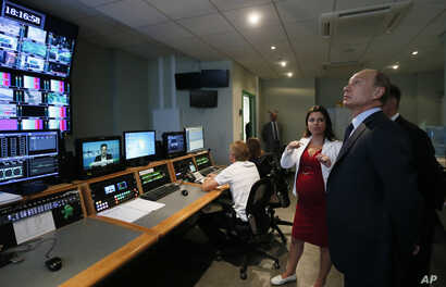 FILE - Russian President Vladimir Putin  visits the headquarters of what was then known as the Russia Today television channel in Moscow, June 11, 2013 Major brands in the export division of Russian media include RT, the RIA Novosti news agency, Sput...