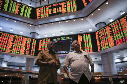 A couple watches trading boards at a private stock market gallery in Kuala Lumpur, Malaysia, Tuesday, Aug. 25, 2015.