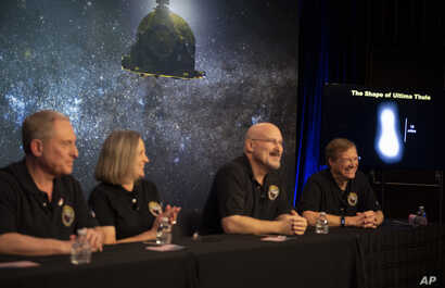 A new image of Ultima Thule, right, is displayed during a press conference featuring, from left, principal investigator Alan Stern, operations manager Alice Bowman, systems engineer Chris Hersman, and project scientist Hal Weaver.