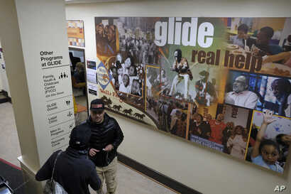 In this  Feb. 12, 2019 photo, people walk past a display and directory to the many assistance programs at the Glide Memorial United Methodist Church in San Francisco.