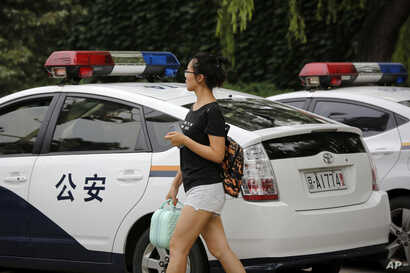 Ren Liping walks by police vehicles parked outside the police headquarters as she prepares to file a petition for her case to be re-examined in Beijing.