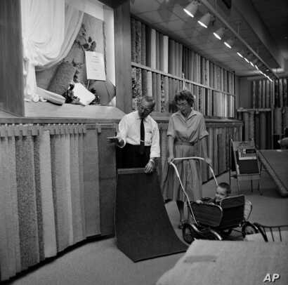 A customer examines carpet samples at Sears Roebuck department store in Niles, Illinois, Aug. 23, 1961.