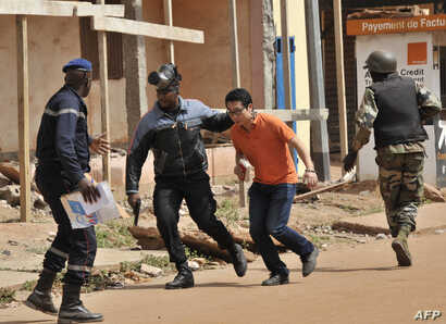 Malian security forces evacuate a man from an area surrounding the Radisson Blu hotel in Bamako, Nov. 20, 2015.