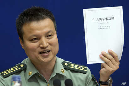 FILE - China's Defense Ministry spokesman Yang Yujun holds up a report on China's Military Strategy in Beijing, China, May 26, 2015. Yang criticized a U.S. report assessing China's island-building efforts in the South China Sea.