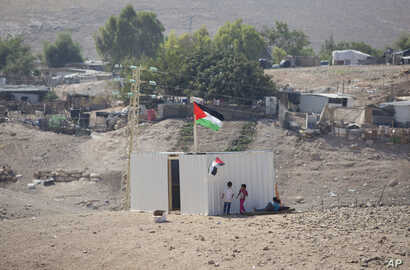 Palestinian girls sit by a newly made shed in the West Bank Bedouin community of Khan al-Ahmar, Sept. 11, 2018. Israel says Khan al-Ahmar was illegally built and has offered to resettle residents 12 kilometers (7 miles) away.