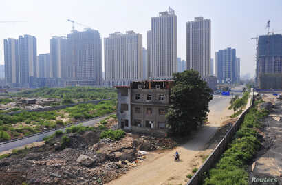 FILE - A man rides his bicycle past a partially demolished building in the middle of a street next to new residential construction sites in Xi'an, August 14, 2013.