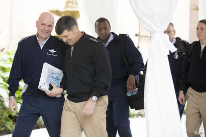 FILE - Air Force Gen. Carlton D. Everhart, the Commander of Air Mobility Command, left, holds a binder with a photograph of Air Force One on the cover as he speaks to Navy Adm. Bill Moran, Vice Chief of Naval Operations, second from left, while arriv...