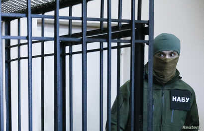 FILE - A member of the National Anti-Corruption Bureau of Ukraine stands guard next to a defendant's cage during a court hearing in Kyiv, Ukraine, April 21, 2017.