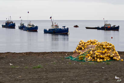 FILE - Fishing boats are seen near the village of Rybaki on Iturup Island, in the Russian Far East, Aug. 20, 2011.