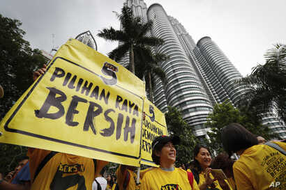"""Activists from the Coalition for Clean and Fair Elections (BERSIH) show a placard reading """"Clean Election BERSIH"""" in front of the Petronas Towers during a rally in Kuala Lumpur, Malaysia Saturday, Nov. 19, 2016."""