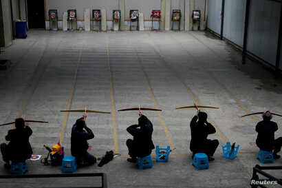Ethnic Lisu men aim their crossbows during a crossbow shooting training session at Lushui Crossbow Stadium of Nujiang Lisu Autonomous Prefecture in Yunnan province, China, March 27, 2018.