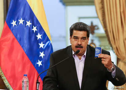 Venezuela's President Nicolas Maduro holds a copy of the Venezuelan constitution while he speaks during a meeting with members of the Venezuelan diplomatic corp after their arrival from the United States, at the Miraflores Palace in Caracas, Venezuel...