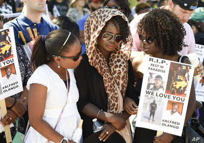 Two friends console Winnie Olango, center, sister of Alfred Olango, before a march Oct. 1, 2016, in  El Cajon, Calif. Alfred Olango, a Ugandan refugee, was unarmed and in mental distress when he was shot by an El Cajon police officer Tuesday.