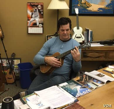 Michael Upton relaxes by playing his ukulele in his office at the Kala Brand Music Company