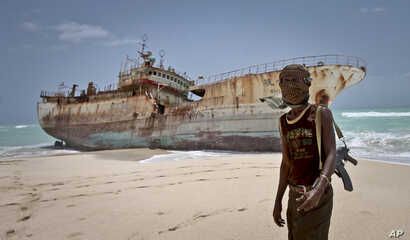 A masked Somali pirate stands near a Taiwanese fishing vessel that washed up on shore after the pirates were paid a ransom and released the crew, in the once-bustling pirate den of Hobyo, Somalia, Sept. 23, 2012.