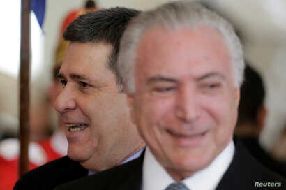 Paraguayan President Horacio Cartes smiles next to Brazil's President Michel Temer at the Mercosur trade bloc annual summit in Luque, Paraguay, June 18, 2018.