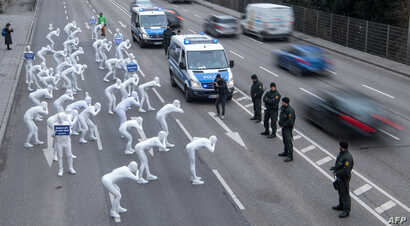 Greenpeace activists wear white morphsuits as they stage an action against particulate matter and health burden caused by diesel exhaust on February 19, 2018 in Stuttgart, southern Germany.