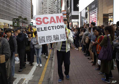 A pro-democracy protester displays a sign during a demonstration in Hong Kong to demand genuine universal suffrage, March 25, 2017.