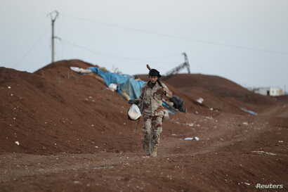 A rebel fighter from Jaysh al-Sunna carries food as he walks along a sand barricade in Tel Mamo village, in the southern countryside of Aleppo, Syria, March 13, 2016.