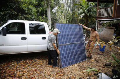 Edwin Montoya, left, and Abe Pedro, load a solar panel removed from the Montoya family's property onto a truck, May 18, 2018, near Pahoa, Hawaii. Montoya family owns a farm near Pohoiki Road and lava crossed the road near his property, Friday, blocki...