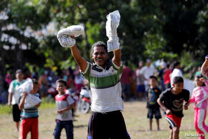 A man holds up supplies after an Indonesian Red Cross helicopter dropped aid to the earthquake affected area in Sirenja, Donggala Regency, Central Sulawesi, Indonesia, Oct. 5, 2018.