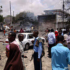 People mill around the scene where a suicide attack took place in Somalia's capital Mogadishu, October 4, 2011.