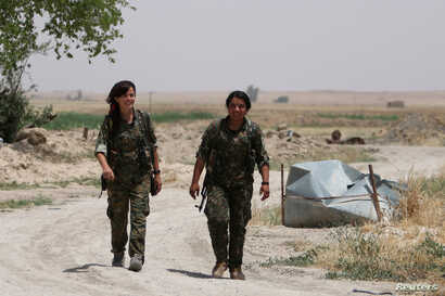 FILE - Kurdish female fighters from the People's Protection Units (YPG), operating alongside with the Syria Democratic Forces, walk in northern province of Raqqa, Syria, May 27, 2016.