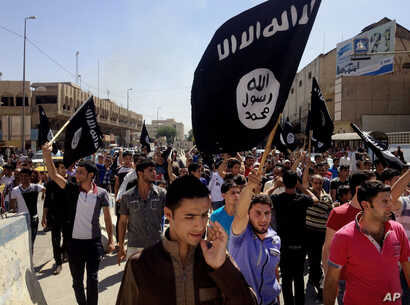 FILE - Young men chant pro-Islamic State slogans as they wave the group's flags in Mosul, Iraq.