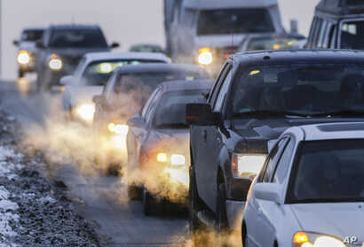 FILE - Car exhaust billows around commuter traffic in winter weather in Omaha, Nebraska, Feb. 1, 2013.