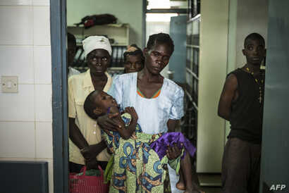 FILE - An HIV positive mother holds her sick child at the Thyolo District hospital in Malawi, Nov. 26, 2014.
