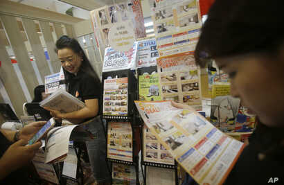 FILE - In this June 24, 2016 photo, visitors read leaflets on hotels in Japan at the Japan Tourism Fair in Bangkok, Thailand.