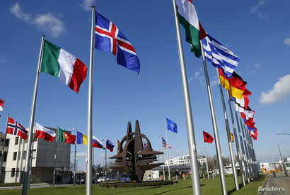 FILE - Flags fly at the NATO headquarters in Brussels.