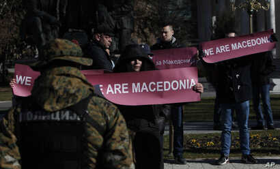 "A group of people hold banners reading ""We are Macedonia"" during an anti-NATO protest in front of the Parliament in Skopje, Macedonia, while NATO Secretary General Jens Stoltenberg addresses the lawmakers in the Parliament building, Jan. 19, 2018."