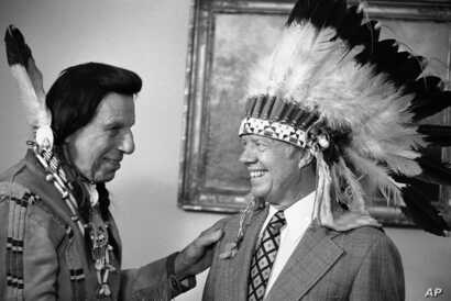 FILE - This photo shows Iron Eyes Cody, an Italian American famous for fabricating Native American identity,. Seen here presenting former President Jimmy Carter with a Native American headdress in the Oval Office in Washington on April 21, 1978.