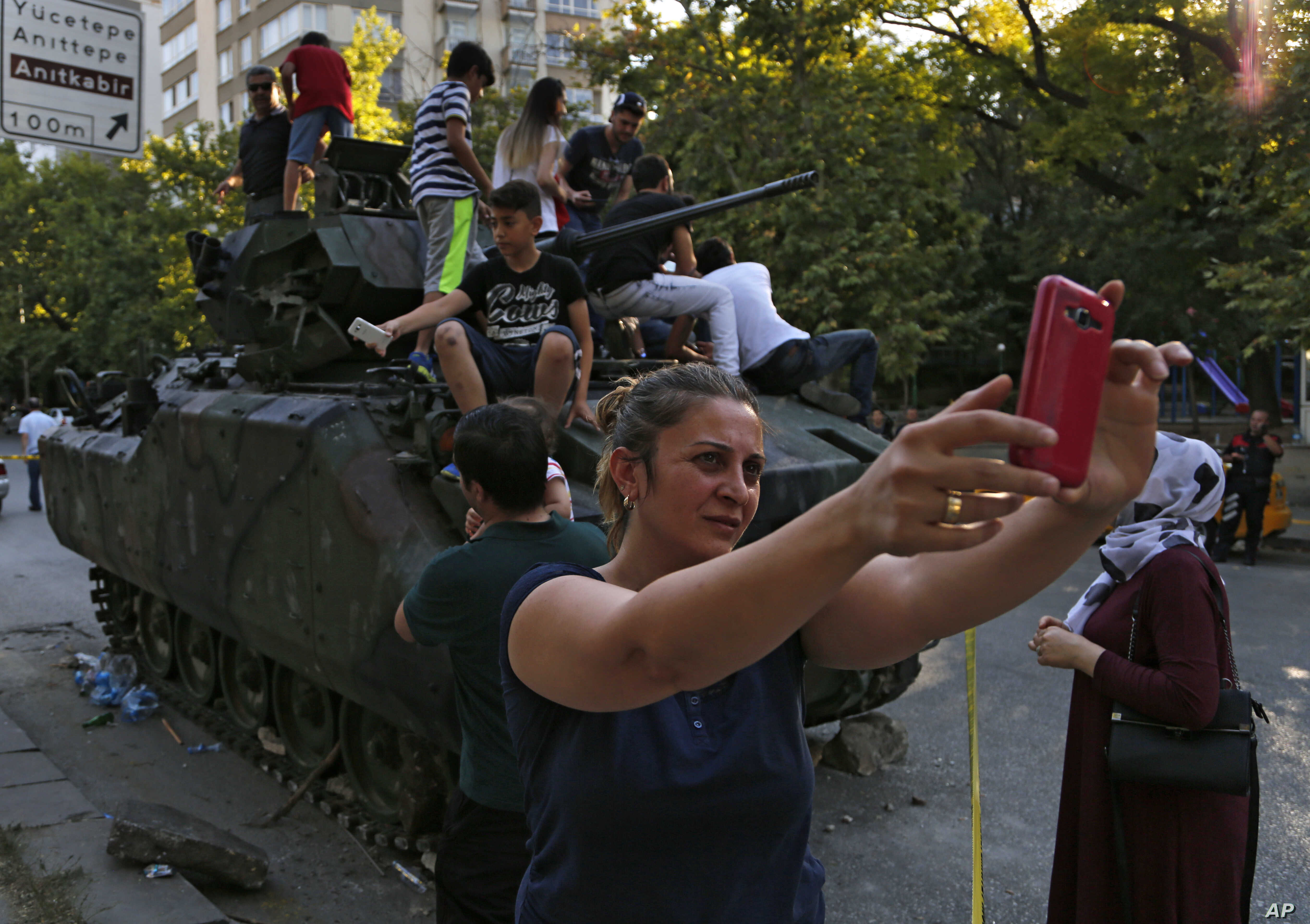 A woman takes a selfie in front a damaged Turkish military armored personnel carrier that was attacked by protesters near the Turkish military headquarters in Ankara, July 16, 2016.