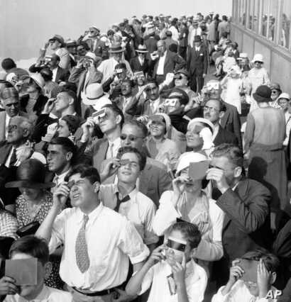 FILE - Eclipse watchers squint through protective film as they view a partial eclipse of the sun from the top deck of New York's Empire State Building in New York, Aug. 31, 1932.