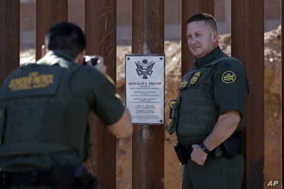 FILE - Border Patrol agent Michael Sullivan (R) poses for a picture next to a plaque adorning a newly fortified border wall structure in Calexico, Calif., Oct. 26, 2018.