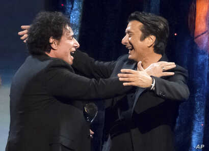 Inductees Neal Schon, left, and Steve Perry from the band Journey embrace at the 2017 Rock and Roll Hall of Fame induction ceremony.